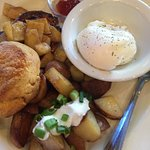 Country breakfast, pork chop and apples, potatoes, poached eggs, and biscuit.