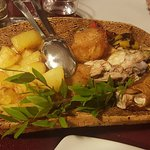 Maialetto in crosta con patate arrosto su pane carasau.