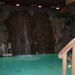 The indoor pool has a waterfall at the deep end of the pool.
