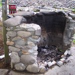 Stone grill for guests to use, also picnic table & chairs.