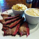 Smoked brisket with cheesy grits and mac and cheese.
