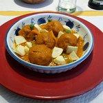 Albóndigas vegetales con salsa y patatas fritas.