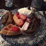 Waffles with homemade whipped cream, fresh fruit, and sausage