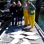Assorted day's catch & happy anglers with guide