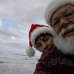 vacationing Santa and Mrs talking a walk at the beach