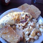 Meat lovers egg omelette, home-made fried potatoes and wheat toast.