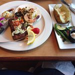 Surf and turf with baked potato and steamed vegetables