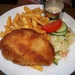 Pork schnitzel with salad and cream sauce.