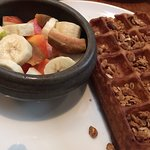 Wheat waffle topped with granola with diced fruit