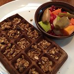Gluten free waffle topped with granola with diced fruit