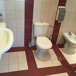 Et kæmpe badeværelse med stort spejl over vasken, toilet, fodvask, bruser og badekar
