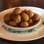 Fried olives served on top of a bowl of marinara