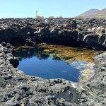 Ecco la piscina come ti appare tra le rocce, con sfondo sul faro