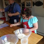 Milly weighs her dough out under David's watchful eye