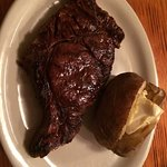 Large ribeye with baked potato with butter