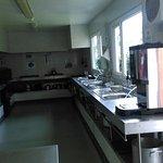 Salon, vue de la salle à manger sur le salon, cuisine collective et casiers individuels dans la