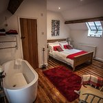 large bedroom with luxurioous free standing bath and separate ensuite toilet and sink bath