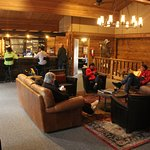 Upstairs in the main lodge with bar against the far wall, seating area, and family game/reading