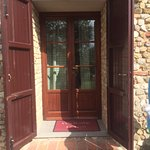 standing outside in the garden, entrance to the apartment, a small table and chairs are to the s