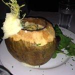 Camarão no Coco Sautéed shrimps with mushrooms and herbs, coconut milk served in a fresh coconut
