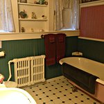 Bathroom with claw-foot bathtub and strong sulfur smell in water.