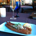 half order of fried asparagus with crab meat; prosecco wine; bar visible in the background