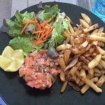 Superbe tartare de saumon tranché au couteau avec son accompagnement de salade et de frites avec