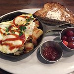 smoked barbecue brisket hash with eggs over medium, fruit, toast and strawberry preserves