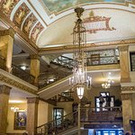 Lobby with ornate ceiling fixtures, paintings, and gilded details.