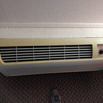 Grimy yellowed AC unit that made the whole room reek of stale cigarette smoke