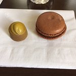 Chocolate with caramel from the painted collection sitting beside a chocolate macaroon