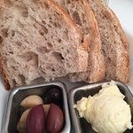 Homemade crafted bread, butter and delicious marinated olive and garlic