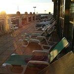 Terrasse de la piscine avec vue port et mer ou coucher soleil.