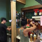 Jake carves the perfect Hawaiian shave ice, while an assistant applies the homemade syrups. Two