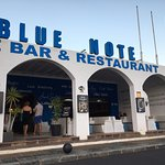 Exterior of The Blue Note from dinner tables opposite by the Marina