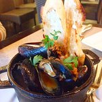 Mussels are cooked with chorizo and served with aioli and baguette slices