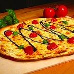 "Unser Flammkuchen ""Caprese"" mit Crème Fraîche, Tomaten, Mozzarella, Basilikum, Balsamico-Creme"