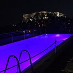 roof top pool at night looking towards the acropolis