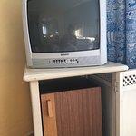 televisión anticuada con botones arrancados y mini nevera viejísima