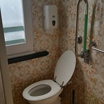 Dated bathroom with very small shower cubicle and far too long shower curtain that got entangled