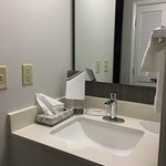 The hotel room and sink area are nicely updated with modern yet comfortable furniture and in tas