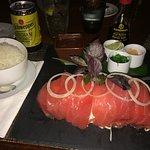 Sashimi de atún, viene con timbal de arroz y sobre una cama de repollo.