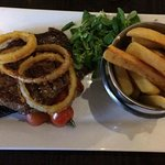 Rib eye steak, mushroom, grilled cherry tomatoes, lambs lettuce onion rings and chips.