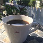 Delicious coffee in sassy mug by the front garden