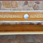 Bench with Summerhill Winery logo for resting outside the main building and restroom.