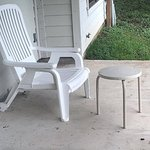 The single lawnchair and table on back porch of cottage.