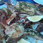 parrillada de pescado congelado bañada en aceite y ajo con perejil