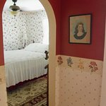 Arched entry to Rose Room. Features vintage paintings,furniture and furnishings.