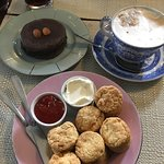 Scones with cream cheese and fresh jam, chocolate alfajor, waffles with dulce de leche