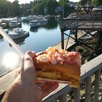 Lobster roll with Perkins Cove in the background